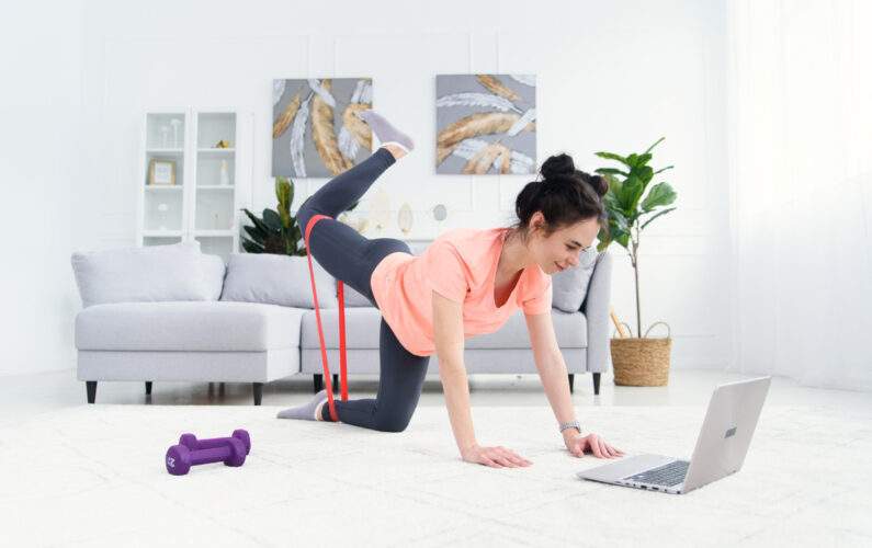 girl-trains-home-online-with-elastic-bands-fitness-online-home-training-woman-with-laptop-sports-home-quarantine